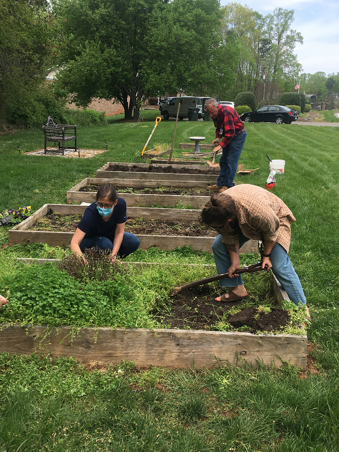 three students work in raised beds