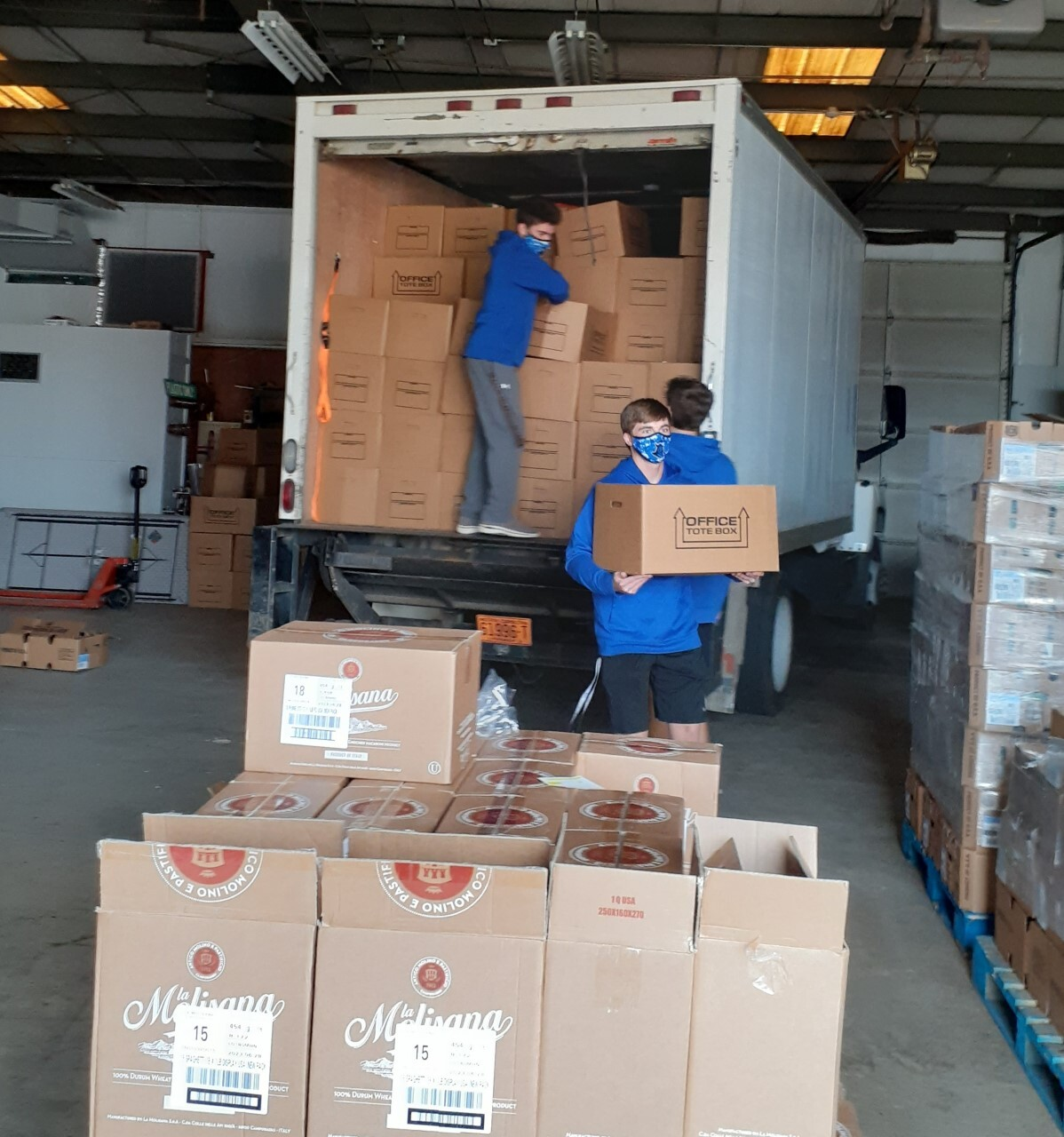Baseball players unload boxes from truck