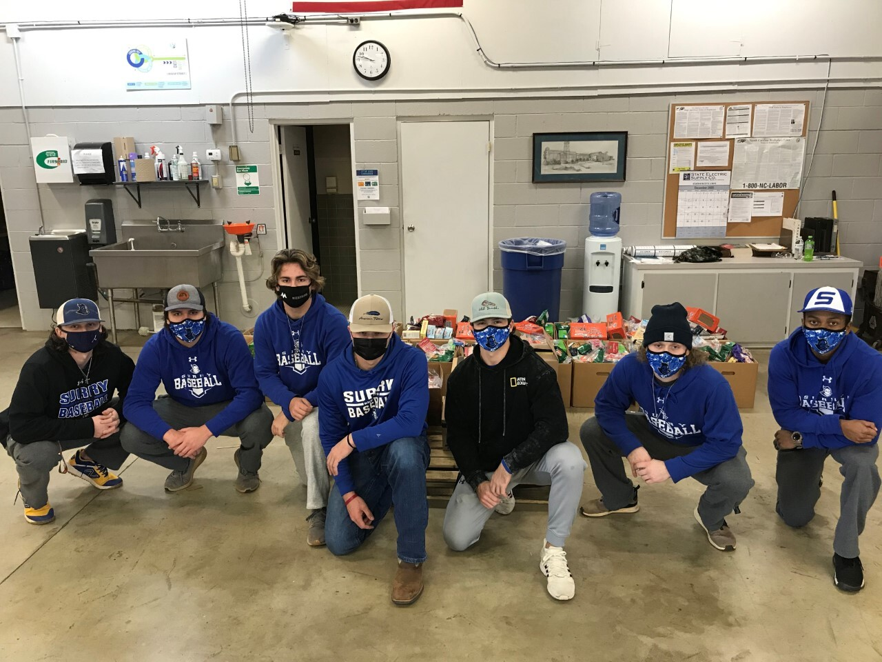 base ball team members post for picture after volunteering time