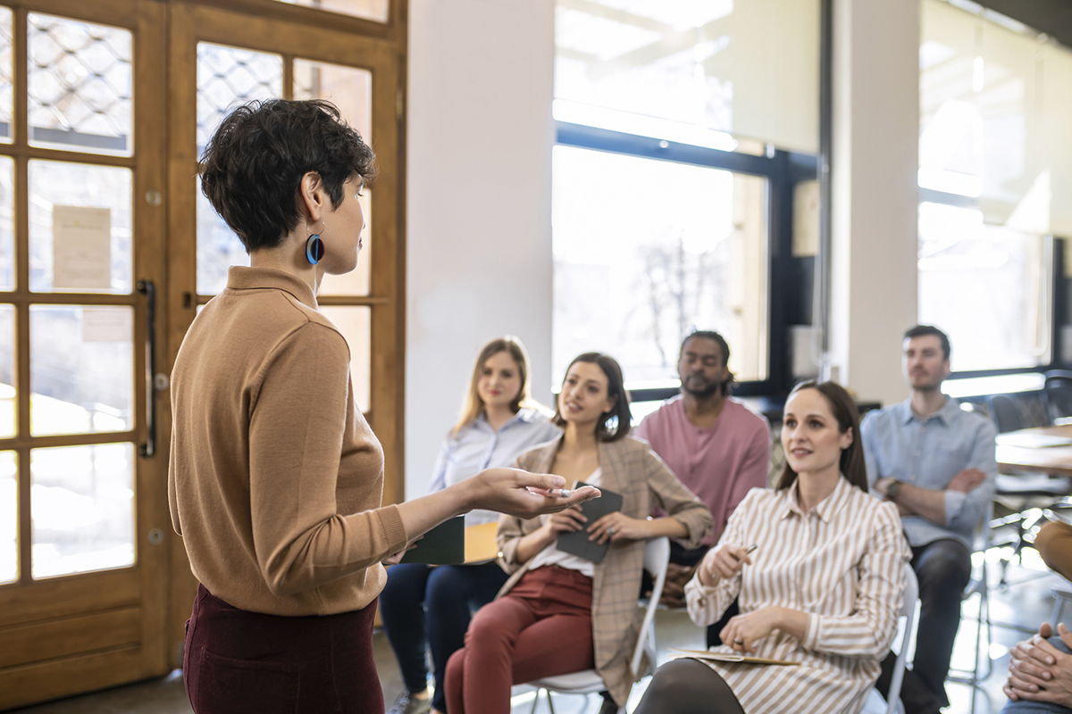 Woman lecturer giving presentation to a group of businesspeople.
