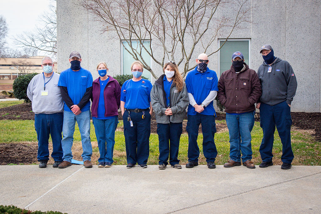 8 members of maintenance staff, in a row, outside building