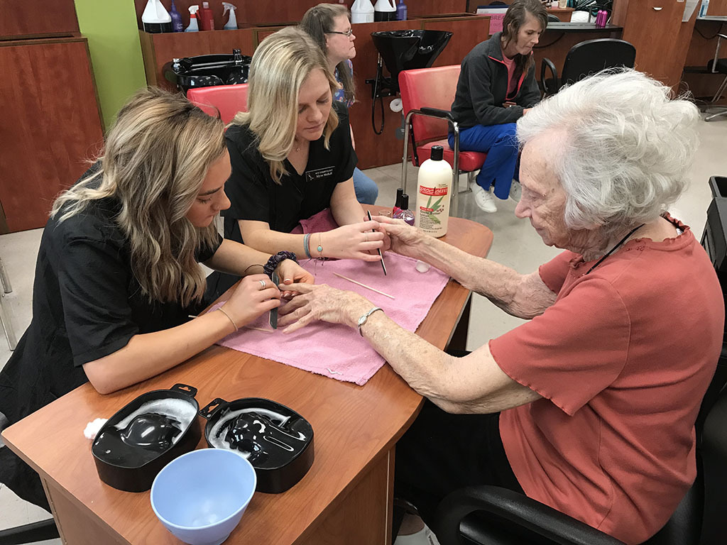 Tristen Moorefield and Klyne Midkiff do a manicure for a Dunmore Plantation resident.