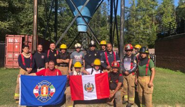 Firefighters from Peru and Colombia pose with their flags