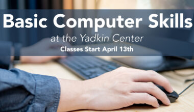 Basic Computer Skills at the Yadkin Center Classes start April 13th. Hand on computer mouse with keyboard.