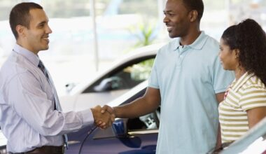 Car dealer shaking hands with male, female, car, inside dealership