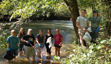 Eight people standing on riverbank at Fisher River Cleanup