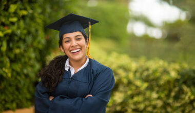 Female student smiling wearing cap and gown.