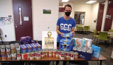 male, inside, standing behind table with stacks of canned food