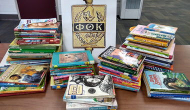 PTK sign with Greek letters surrounded by stacks of children's books on a table