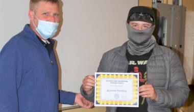 Phillip handing Andrew a certificate