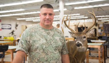 Man standing beside taxidermy deer head buck