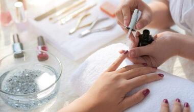 Manicurist painting client's nails