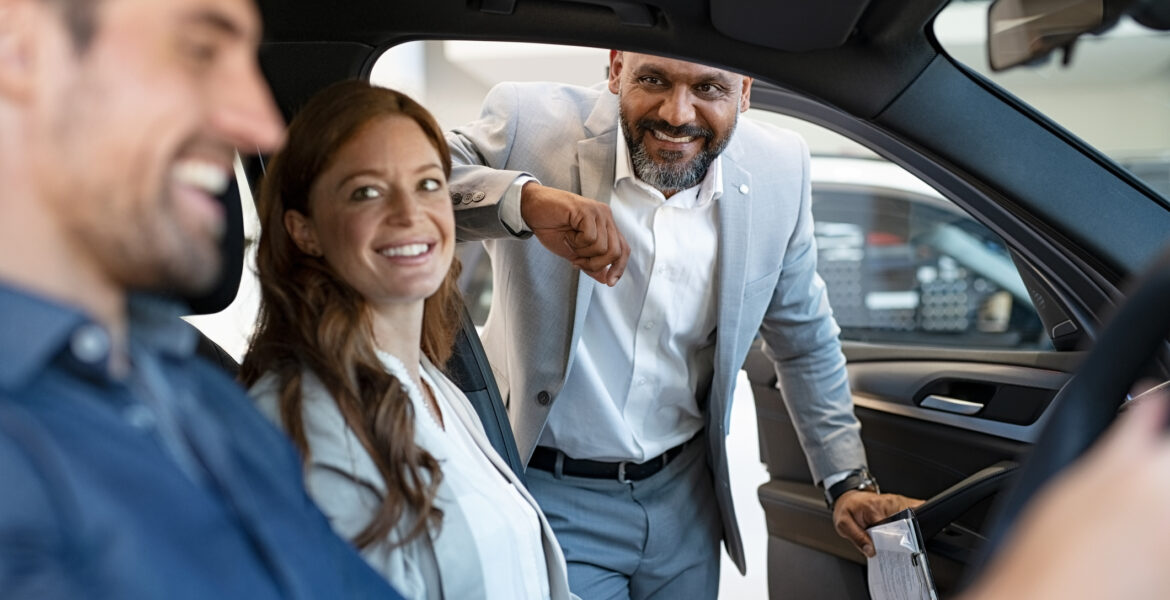 Couple in car with male dealer looking in passenger side