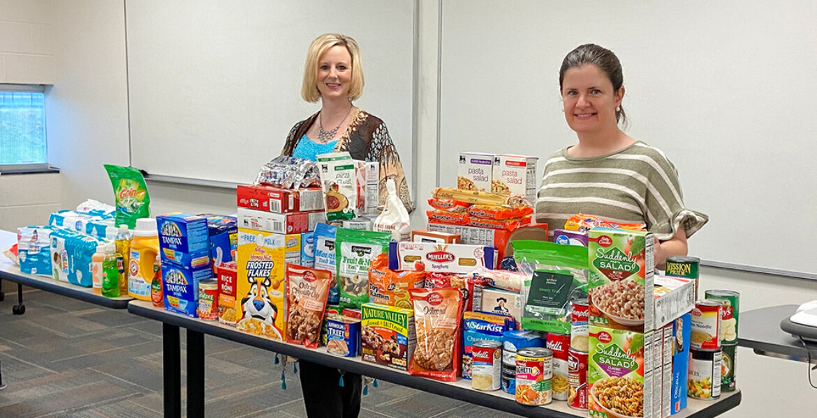 two women standing behind table with food and other donations, inside classroom