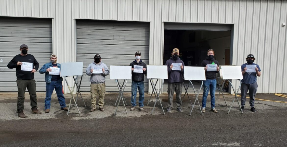 7 males in a row, holding certificates, outside garage like classroom