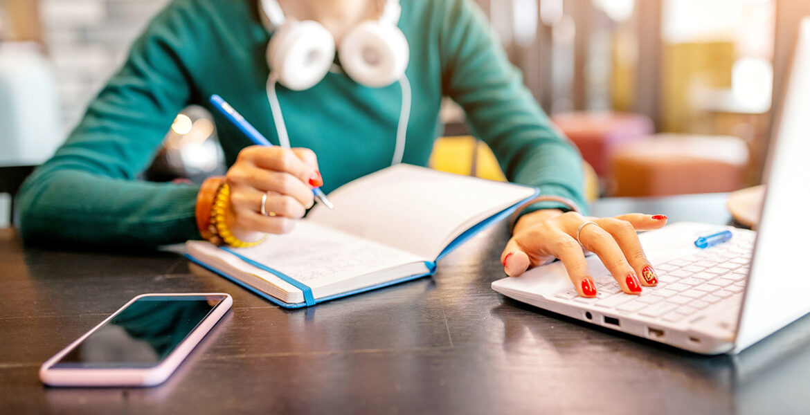 Young happy woman taking notes in notebook and working with laptop