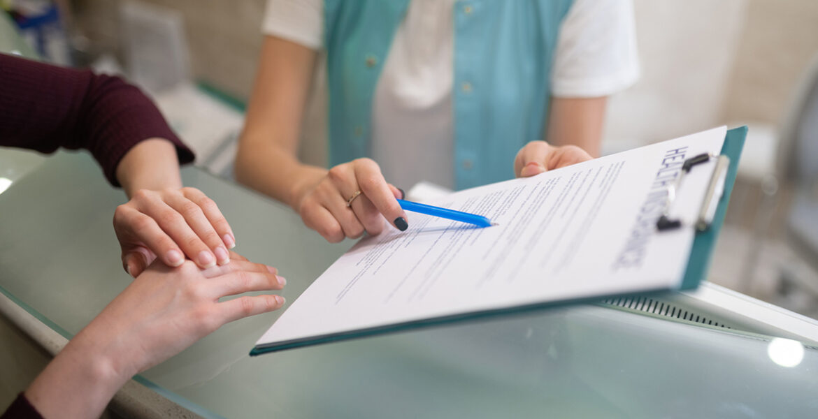 Receptionist of doctors office showing the form to fill in and sign