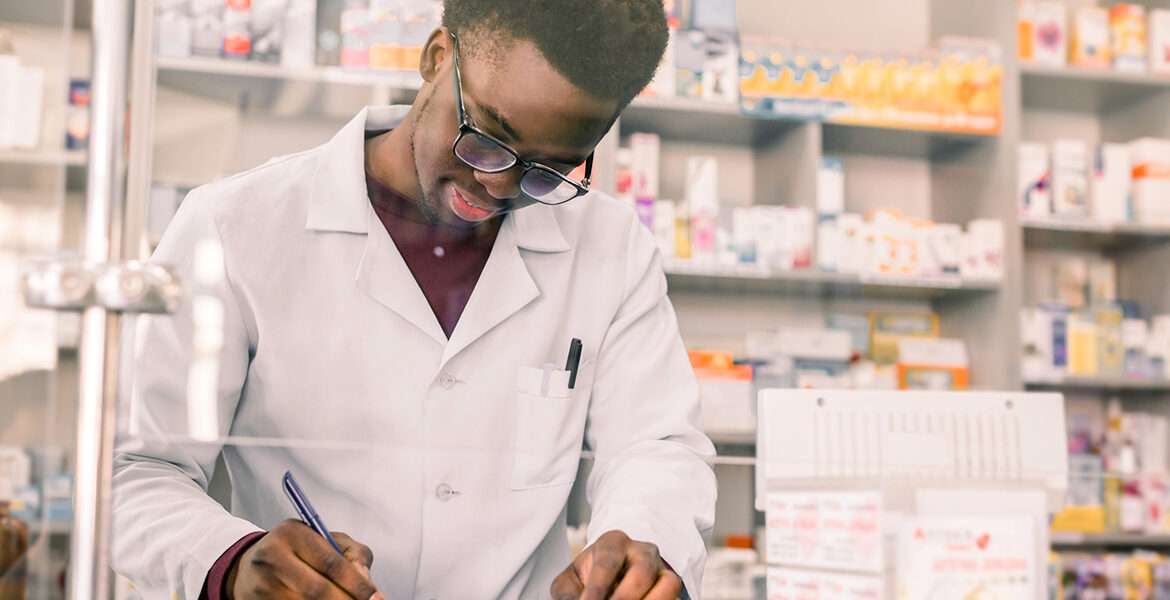 Portrait of a happy African American pharmacist employee writing prescription at workplace in modern pharmacy
