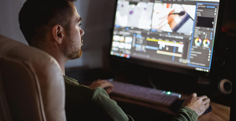 Video montager mounts video at desktop. Home workstation.