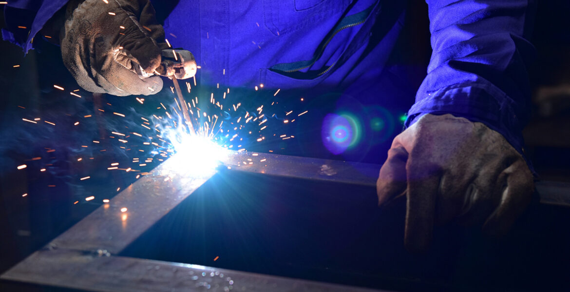 Welder is assembling the workpiece by process shielded metal arc welding (SMAW). Welder in blue uniform, safety shoes, leather gloves, welding mask. He is sitting and welding.