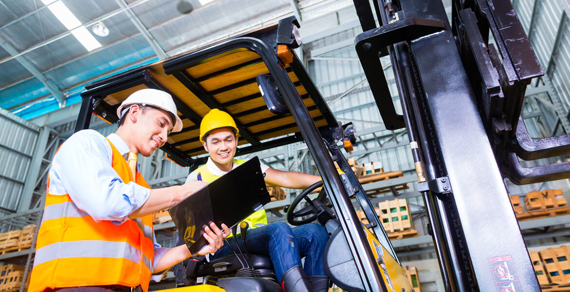 Fork lift truck driver and foreman in storage