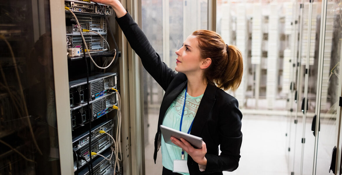 Technician holding digital tablet while examining server