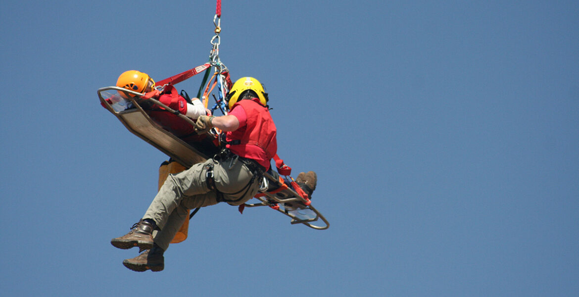 Volunteer rescue worker helping victum from helicopter