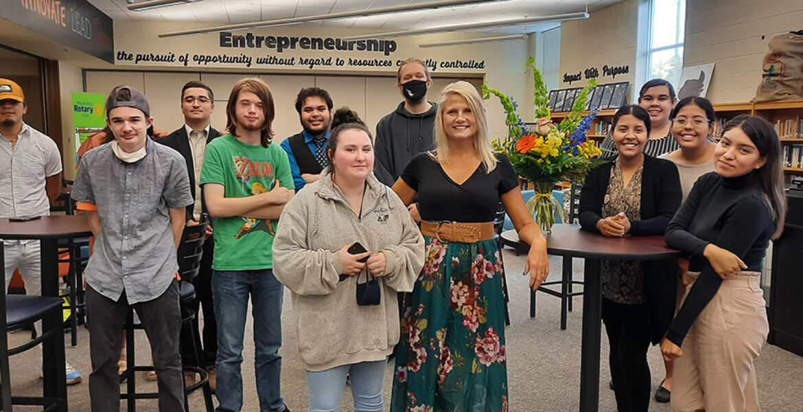 12 people standing inside a classroom. Sigh in back reads Entrepreneurship