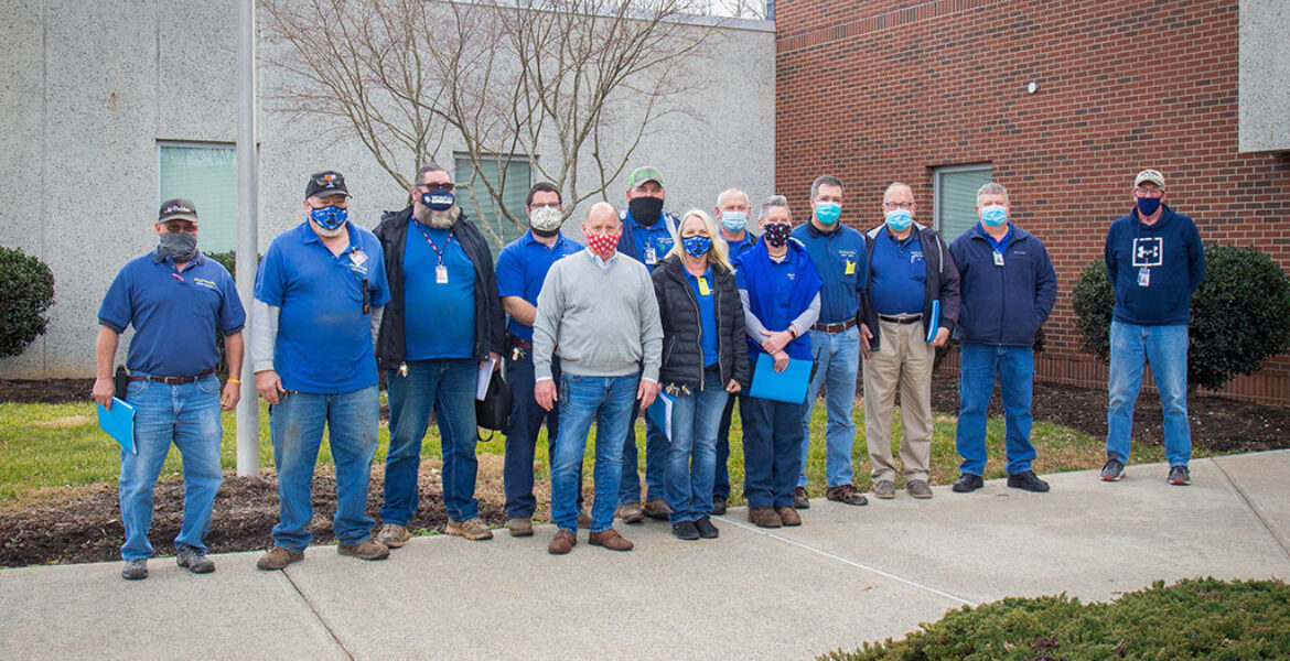 13 Maintenance Staff members in a row, outside building