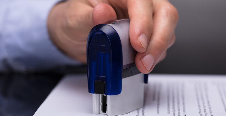 man's hand using stamp to mark document