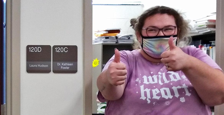 female inside doorway giving thumbs up