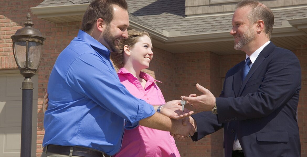 Couple getting keys to new house from their real estate agent.