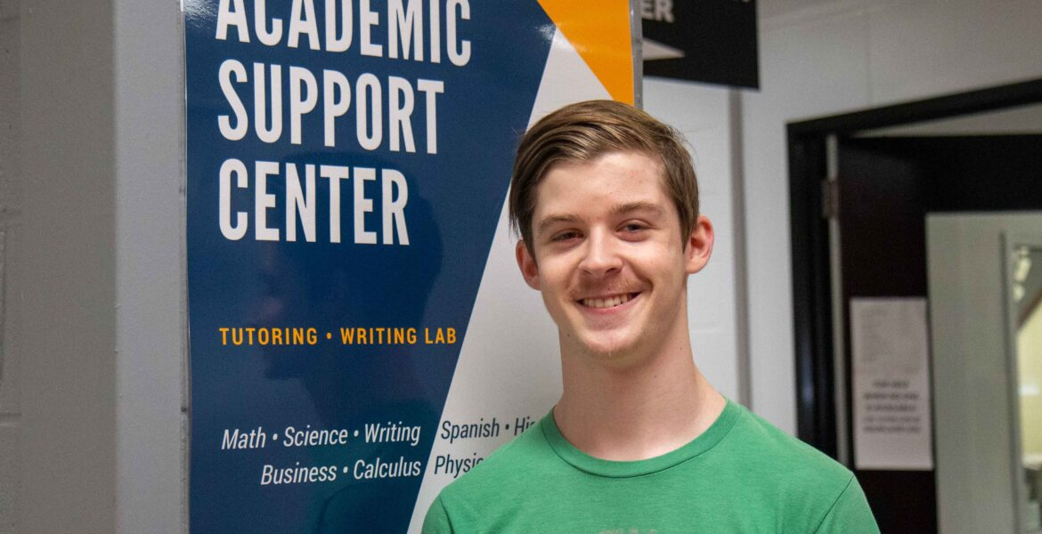 Reed Morgan standing beside Academic Support Center sign, smiling