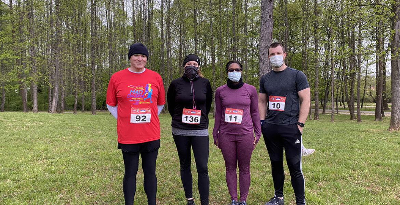 one man, two women, one man standing side by side, outside, wearing running apparel.