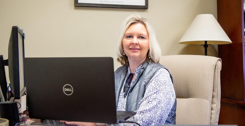 woman sitting at desk using computer