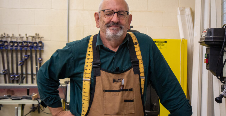 Tony Suess - man with beard, wearing work apron, inside