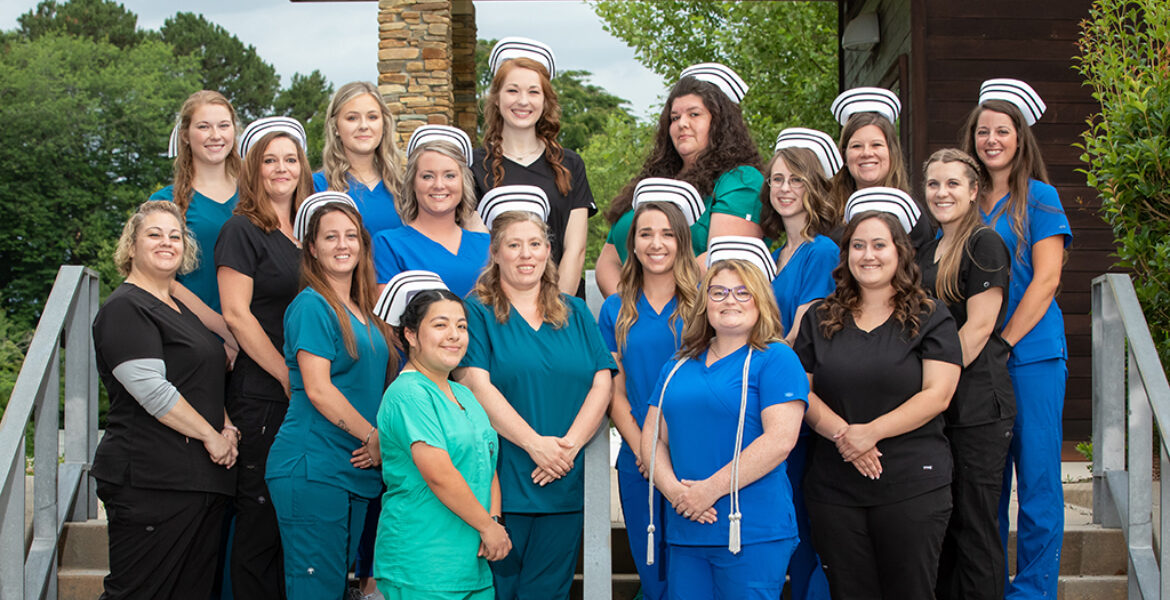 17 women standing on steps, outside, wearing scrubs and nurse's caps
