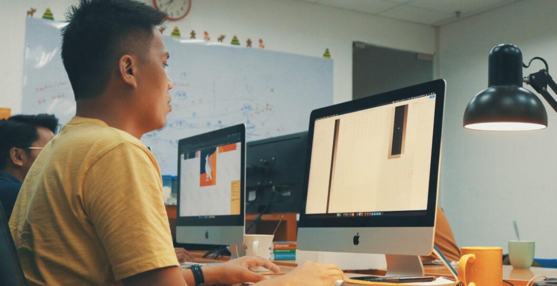 man using Apple desktop inside classroom or office