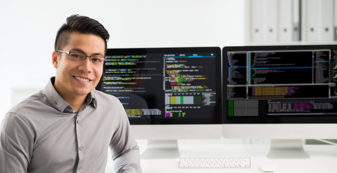 young man facing you with two computer screens in background
