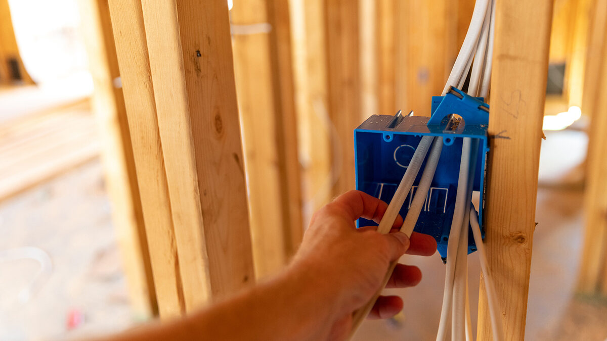 Hand working on electrical wires in new home construction