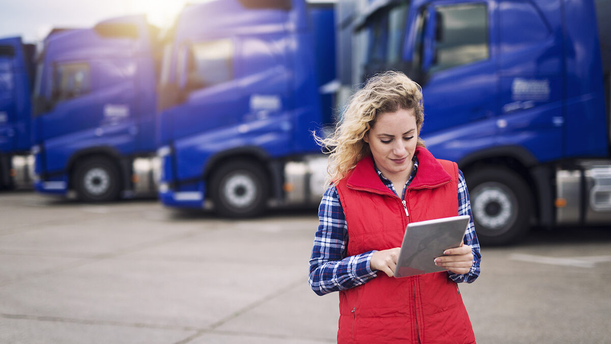 Trucking company employee holding tablet and checking route for new destination. In background parked truck vehicles.