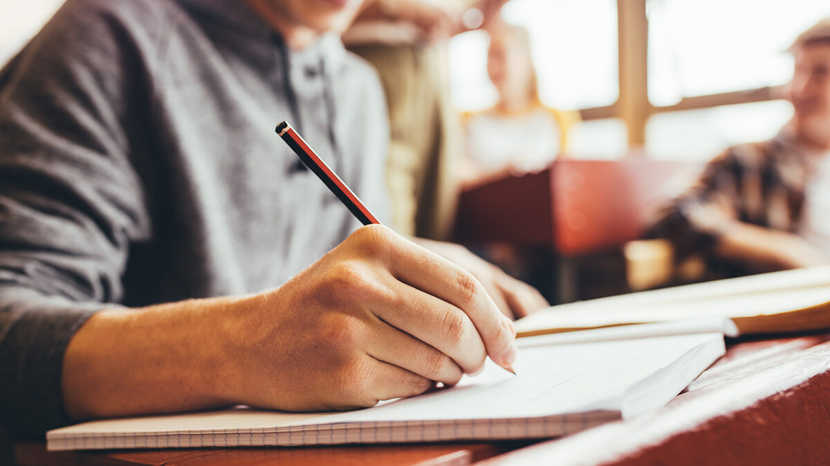 Close up of male student taking notes sitting at desk during lecture in high school. Focus on hand writing in notebook with a pencil.