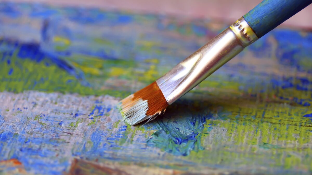 Close up of paint brush on oil painting canvas